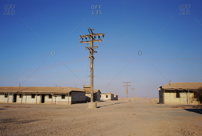 Electricity pylon on field against clear blue sky