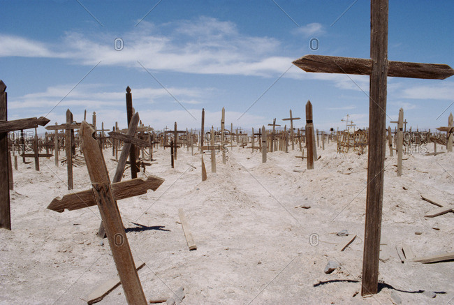 Graves in cemetery against blue sky