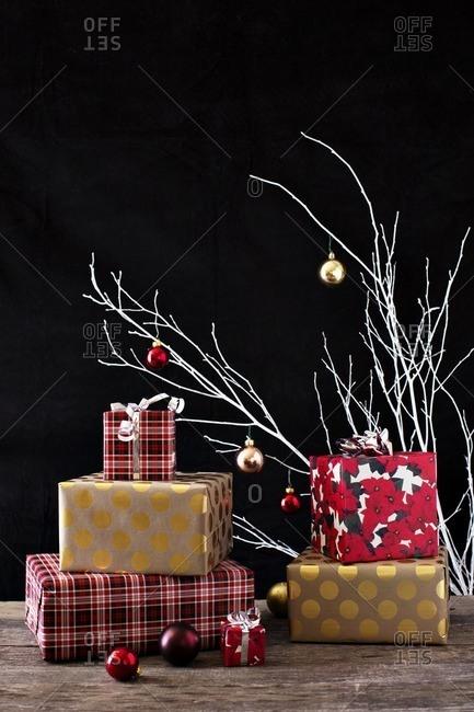 Christmas presents with decoration on wooden table against black background