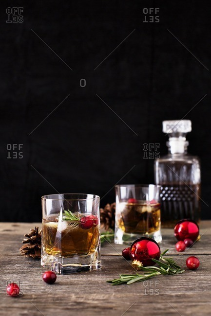 Close-up of drinks with baubles and cranberries on wooden table against black background