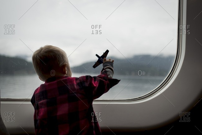 Rear view of boy playing with toy plane while travelling in train