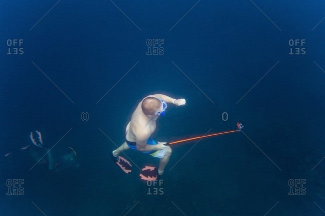 High angle view of man holding monopod while swimming with friends undersea
