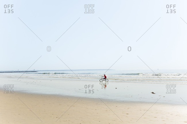 Man riding bicycle at beach against clear sky