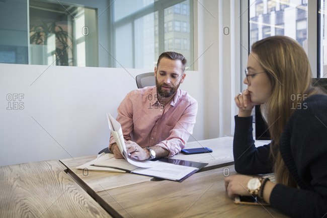 Businessman explaining reports to colleague in office