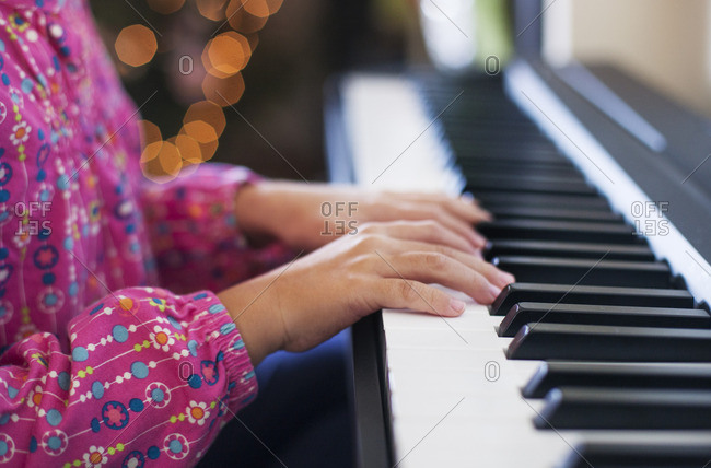 Midsection of girl playing piano while sitting at home