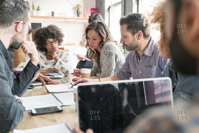 Coworkers examining reports at table in office