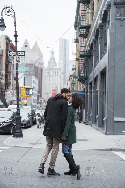 Full length of business couple kissing while standing on city street