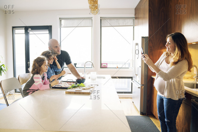Pregnant woman photographing family at kitchen counter in home