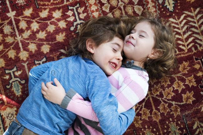 Cute siblings embracing while lying on floor at home