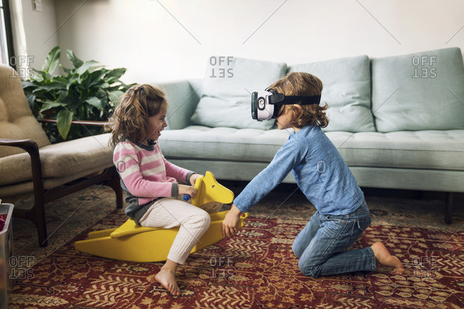 Boy wearing virtual reality simulator playing with sister sitting on rocking horse at home
