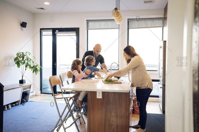 Family preparing food at kitchen counter at home