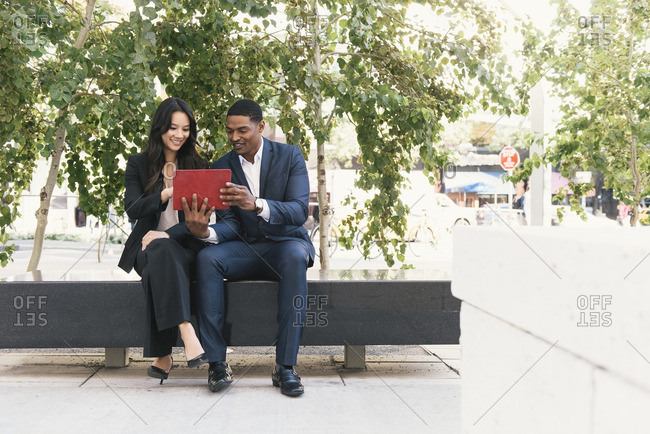Business people using tablet computer while sitting on bench