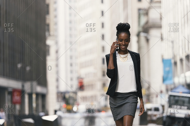 Woman talking on smart phone while walking in city