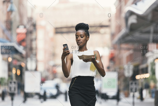 Woman with food and disposable cup using smart phone while walking in city
