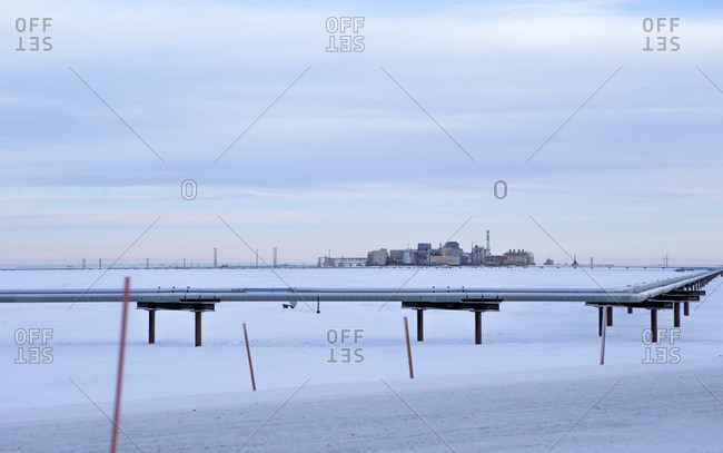 Pipeline on snow covered field against cloudy sky