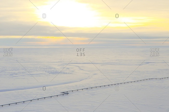 High angle view of pipeline on snow covered field against cloudy sky