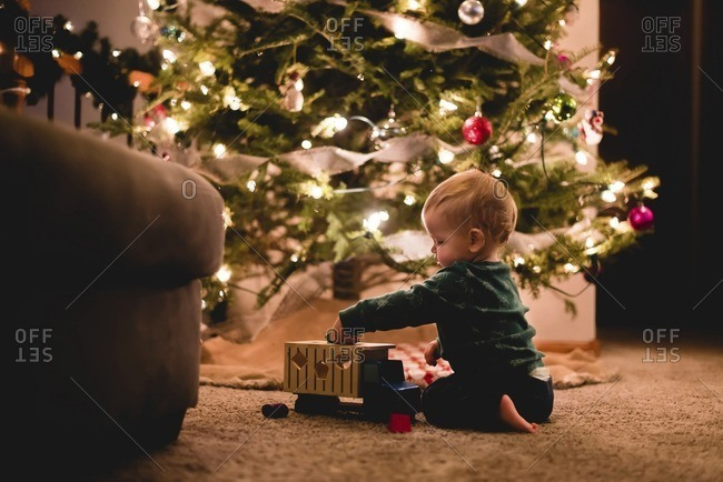 Side view of cute baby boy playing with toy truck by Christmas tree at home