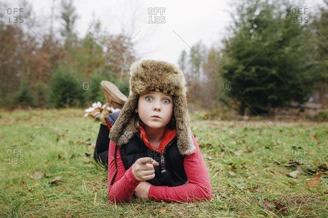 Portrait of girl in hunters cap gesturing while lying on field