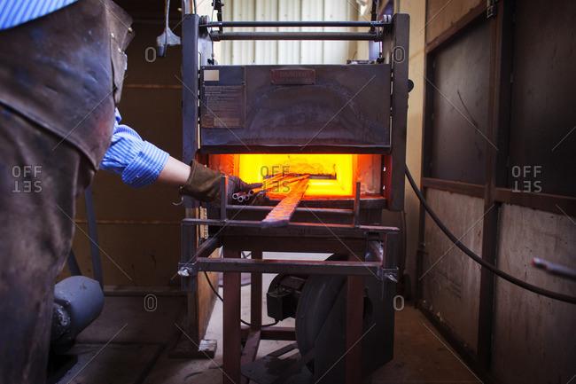 Craftsperson melting metal at factory