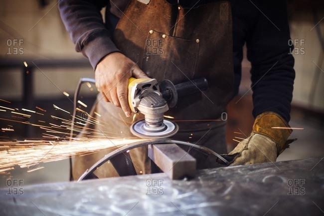 Craftsperson using circular saw while polishing metal at factory