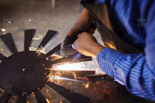 Cropped image of craftsperson welding circular metal at factory