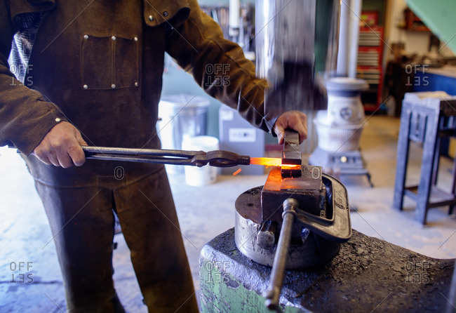 Midsection of craftsperson removing hot metal at factory