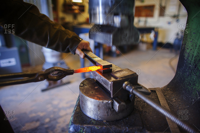 Cropped image of craftsperson removing hot metal at factory