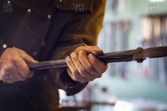Cropped image of craftsperson holding tongs at factory
