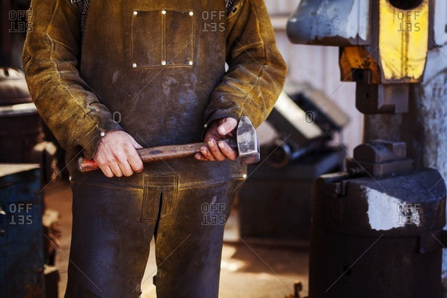 Midsection of craftsperson holding hammer at metal industry