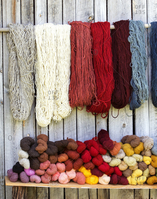 Various strings of wool against fence
