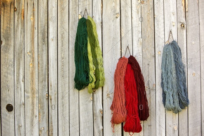 Various strings of wool on fence against workshop