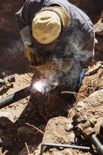 High angle view of craftsperson welding pipe at construction site