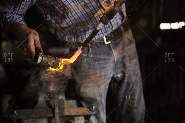 Midsection of craftsperson hammering metal at factory