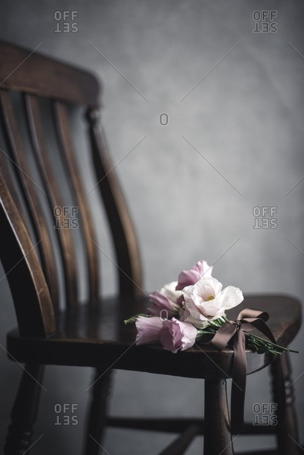 Bunch of flowers on wooden chair in room