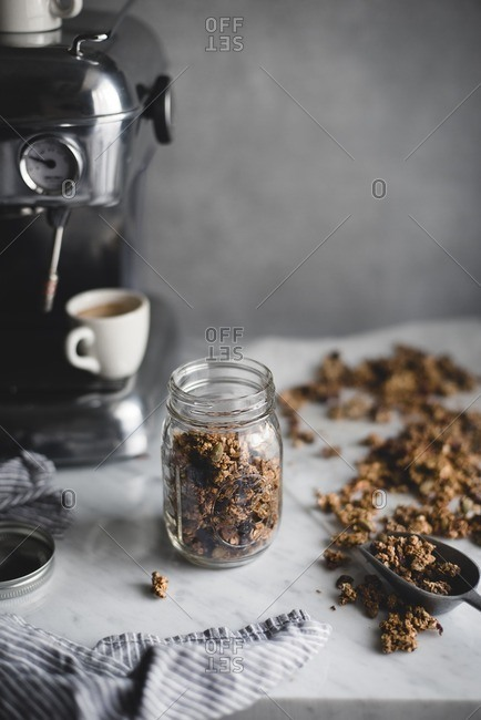 Granola by coffee maker on table