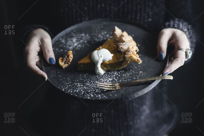 Midsection of woman holding pumpkin pie in plate