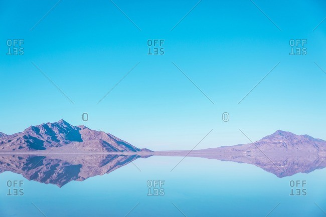 Scenic view of mountains reflecting in lake at Bonneville Salt Flats against blue sky