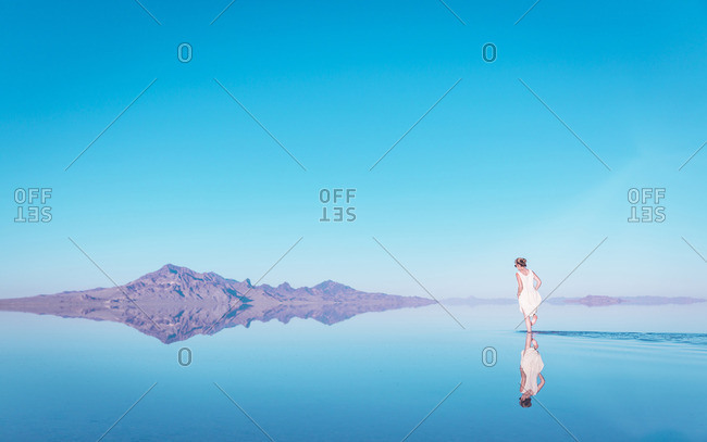 Woman walking in lake by mountain at Bonneville Salt Flats against blue sky