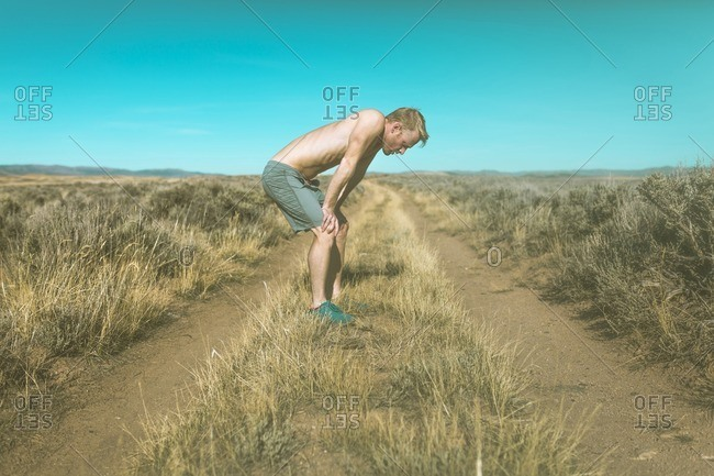 Side view of tired shirtless man relaxing on grassy field against clear blue sky