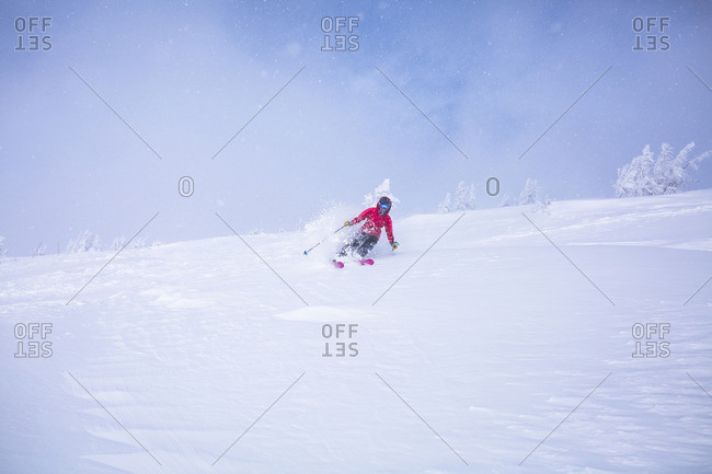 Woman skiing on snow covered landscape against sky