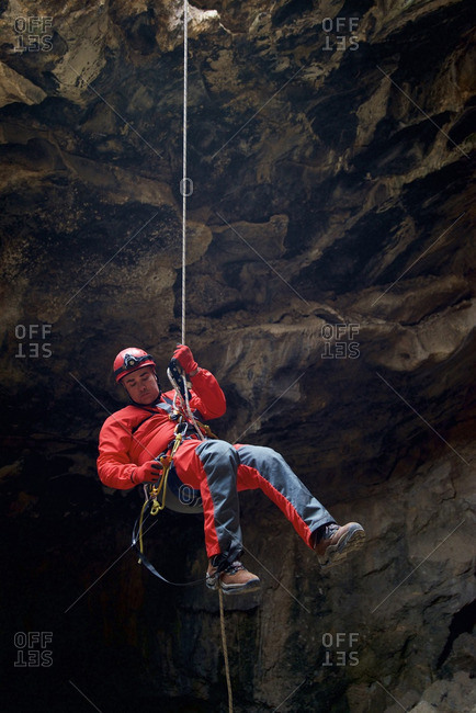 Full length of man hanging on rope by rock formation in cave