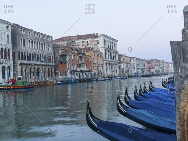Gondolas moored at Grand canal by buildings against clear sky