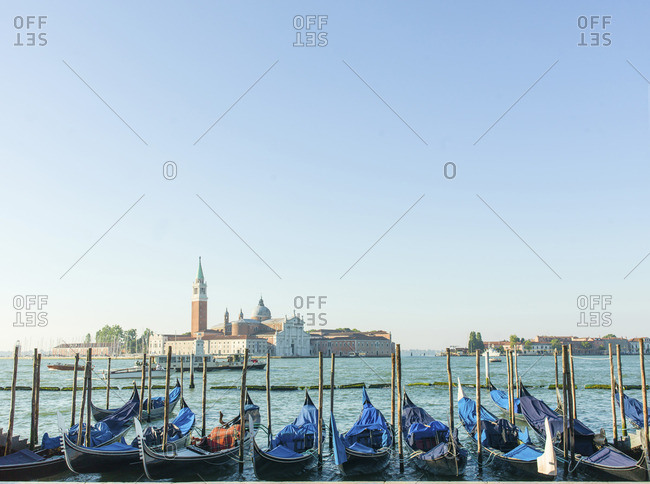 Gondolas moored at Grand Canal in front of city against clear sky
