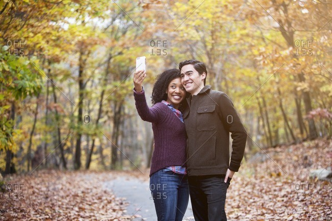 Happy couple taking selfie while standing on footpath in forest
