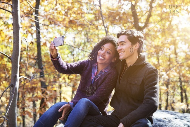 Woman taking selfie while sitting with boyfriend on rock in forest