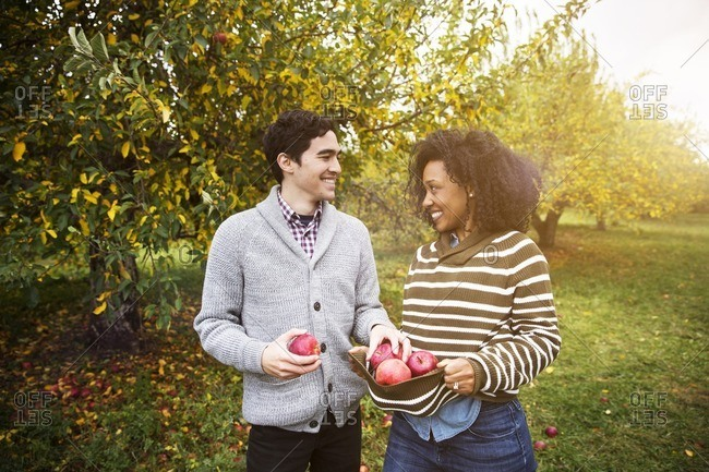 Couple with apples looking at each other while standing in orchard