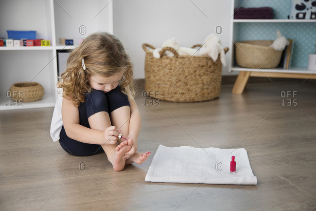 Cute girl applying nail polish to toenails while sitting at home
