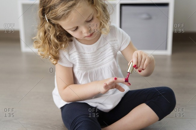 Cute girl applying nail polish on nails