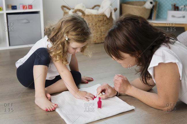 Mother applying nail polish on daughter's fingernails