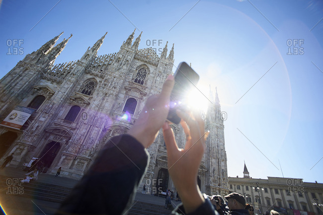 Cropped image of woman photographing Duomo Di Milano against clear blue sky